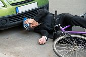foto of accident victim  - Unconscious Male Cyclist Lying On Road After Road Accident - JPG
