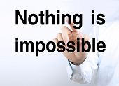 picture of impossible  - Businessman hand is pressing the concept text of Nothing is impossible - JPG