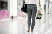 foto of barefoot  - Young woman in office style clothes carrying in hand her high heel shoes walking barefoot in contemporary building legs close - JPG