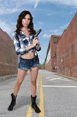 foto of handgun  - Beautiful young woman holding a loaded handgun - JPG