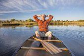 stock photo of collins  - senior male enjoying evening sun on lake in a canoe - JPG