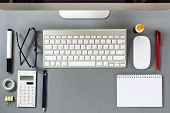 stock photo of neat  - High Angle View of Neatly Arranged Desk Looking Down at Mac Computer Keyboard Mouse and Office Supplies - JPG