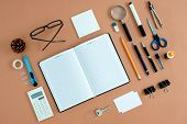 foto of neat  - Assortment of Office Supplies Neatly Organized Around Note Book Open to Blank Page on Desk Top Surface - JPG