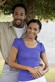 pic of black american  - A happy African American man and woman couple standing outside under a tree and holding hands - JPG