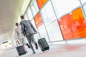 stock photo of carry-on luggage  - Rear view of middle aged businessmen with luggage rushing on railroad platform - JPG