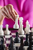 picture of chessboard  - Hand with white queen over chessboard closeup - JPG
