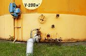 stock photo of fuel economy  - old yellow wall of the fuel tank to an oil storage equipment and pipe - JPG