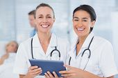 stock photo of clipboard  - Happy doctors looking at clipboard while theirs colleagues speaks with patient in the hospital - JPG