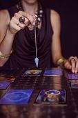 stock photo of fortune-teller  - Fortune teller forecasting the future with pendulum on black background - JPG