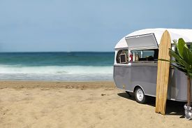 pic of caravan  - Surfing slow food stream line caravan on the beach horizontal template with copy space - JPG