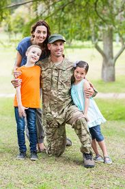 stock photo of reunited  - Handsome soldier reunited with family on a sunny day - JPG