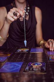 picture of pendulum  - Fortune teller forecasting the future with pendulum on black background - JPG
