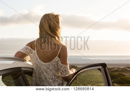 poster of Young traveller woman enjoying sunset standing outside car. Serene woman leaning on car during sunse