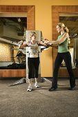 Primeiro adulto caucasianos ajudando feminino maduro adulto caucasianos uso feminino equipamento de exercício no ginásio.