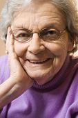 Elderly Caucasian woman smiling with hand on face.