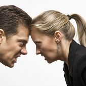 Caucasian mid-adult man and woman with foreheads together staring at each other with hostile express