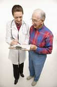 Mid-adult Caucasian female doctor showing papers to elderly Caucasian male.