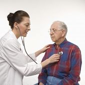 Mid-adult Caucasian female doctor listening  to elderly Caucasian male's heartbeat with stethoscope.