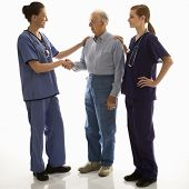 Mid-adult Caucasian female in scrubs shaking hand of elderly Caucasian male with another mid-adult C