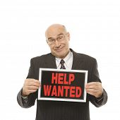 Caucasian middle-aged businessman holding help wanted sign.