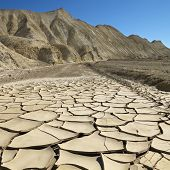 Arrid landscape in Death Valley National Park with dry, cracked ground.