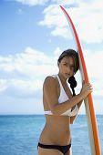Mooie jonge Kaukasische vrouw in bikini leunend op surfplank op strand in Maui Hawaii.