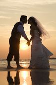 Caucasian mid-adult bride and groom holding hands and kissing barefoot on beach at sunset.