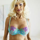 Tan Caucasion blonde middle-aged woman posing in bra.