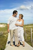 Caucasian mid-adult couple holding each other walking down beach access path.