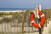 Life preserver hanging on post on beach on Bald Head Island, North Carolina.