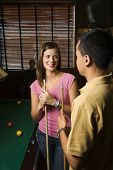 Young man and woman talking and smiling while playing billiards.
