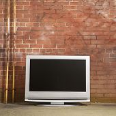 Flat panel television set in front of red brick wall.