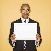 African American man smiling holding blank sign against yellow background.
