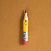 Short number two pencil on tan background.