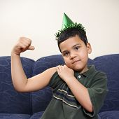 Hispanic boy wearing party hat playfully flexing arm muscle while looking at viewer.