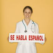 Portrait of Caucasian mid-adult female doctor holding up se habla espanol sign against yellow background smiling and looking at viewer.