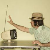 Side view of Caucasian mid-adult man wearing hat sitting at 50's retro dinette set adjusting old tel