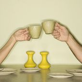 Caucasian mid-adult male and female hands toasting with coffee cups across retro kitchen table setti