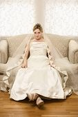 Caucasian bride slouching in love seat.