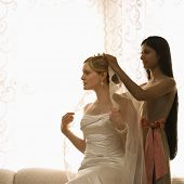 Indian bridesmaid placing veil on Caucasian bride.
