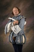 William Shakespeare in period clothing holding feather pen and looking at viewer.