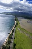 Aerial of road following Maui, Hawaii coastline with beach.