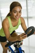Mid adult Asian woman pedaling exercise bicycle smiling at viewer.
