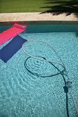 Pink float and vacuum hose in swimming pool.