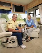 Senior couple sitting in RV holding coffee cups and smiling.