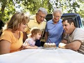 Three generation Caucasian family seated at picnic table celebrating female child's birthday with cake.