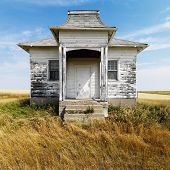 Facade of weathered abandoned building with peeling paint in grasslands.
