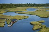 Aerial view of two teenage boys fishing from dock in marshy lowlands of Bald Head Island, North Caro