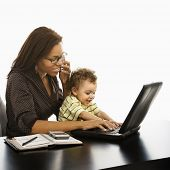 African American businesswoman at work on laptop and cell phone with toddler son on lap.