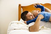 Caucasian toddler boy and father playing and tickling in bed.